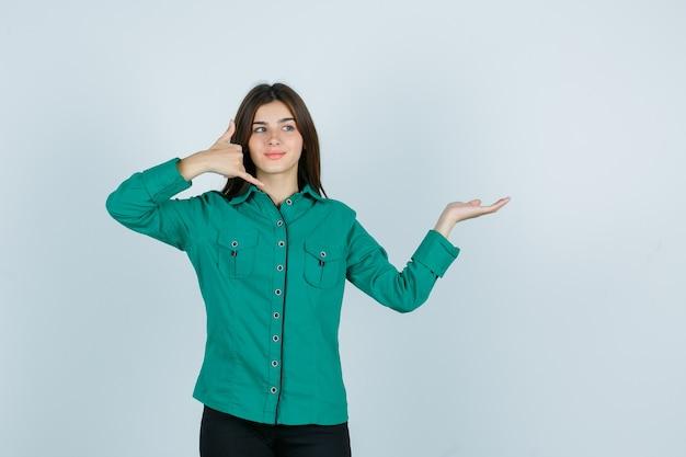 緑のブラウスを着た若い女の子、電話のジェスチャーを示す黒いズボン、手のひらを脇に広げて楽観的な顔をしている、正面図。