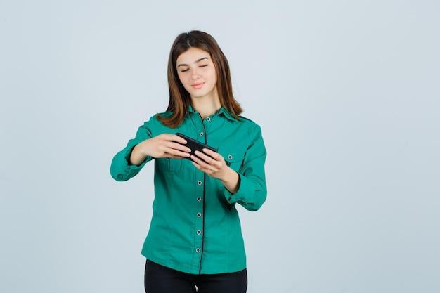 Молодая девушка в зеленой блузке, черных штанах смотрит видео по телефону и смотрит сосредоточенно, вид спереди.
