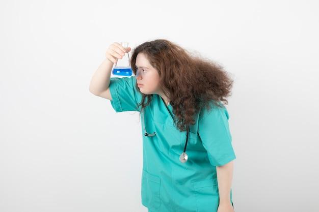 Молодая девушка в зеленой форме держит стеклянную банку с голубой жидкостью.