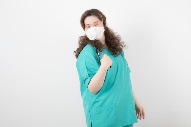 의료 마스크를 쓰고 녹색 제복을 입은 어린 소녀.