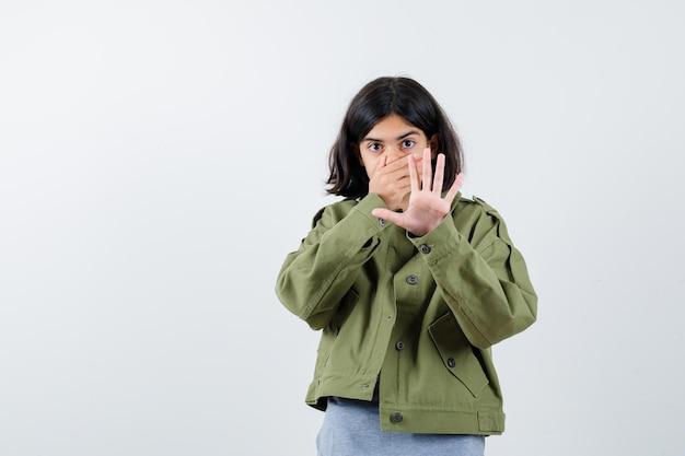 회색 스웨터, 카키색 재킷, 진 바지를 입은 어린 소녀가 입을 덮고 정지 신호를 보여주고 놀란 표정을 짓고 있습니다.