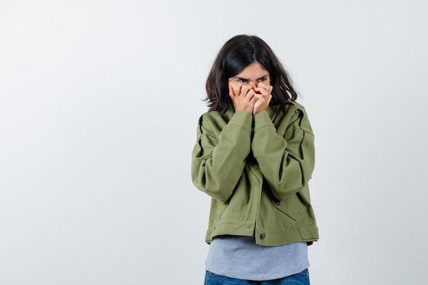 회색 스웨터, 카키색 재킷, 진 바지를 입은 어린 소녀가 손으로 입을 가리고 소심한 앞모습을 보고 있습니다.