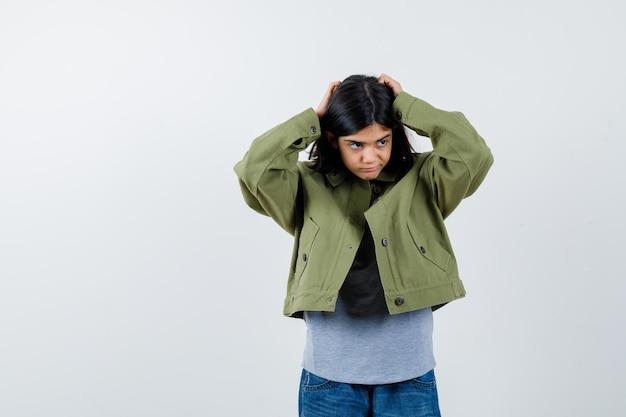 Молодая девушка в сером свитере, куртке цвета хаки, джинсовых штанах, держась за голову, глядя в сторону и задумчиво, вид спереди.