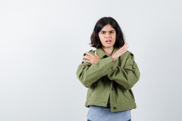 灰色のセーター、カーキ色のジャケット、2本の腕を組んでいるジーンズパンツ、身振りで示すことなく、真剣に見える、正面図の少女。