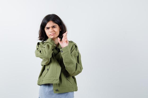 灰色のセーター、カーキ色のジャケット、指を交差させて真剣に見えるジーンズパンツ、正面図の若い女の子。