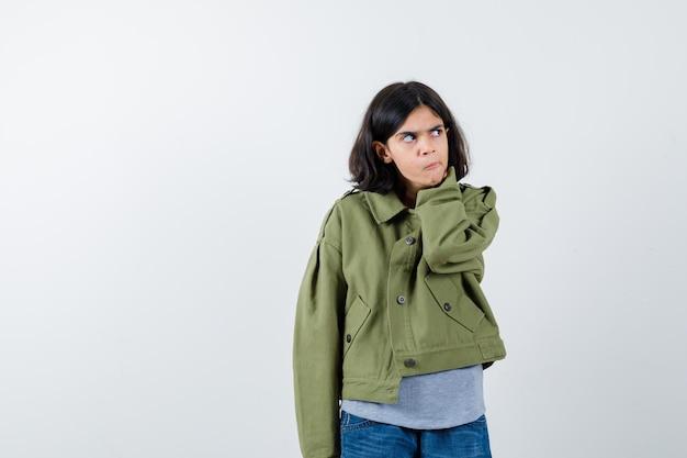 灰色のセーター、カーキ色のジャケット、首に手を置くジーンズパンツ、目をそらし、真剣に見える、正面図の若い女の子。