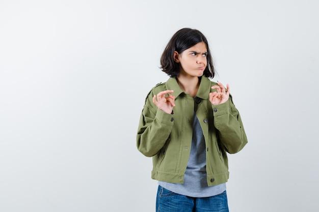 灰色のセーター、カーキ色のジャケット、降伏のジェスチャーで手のひらを上げ、猛烈に見えるジーンズパンツ、正面図の若い女の子。