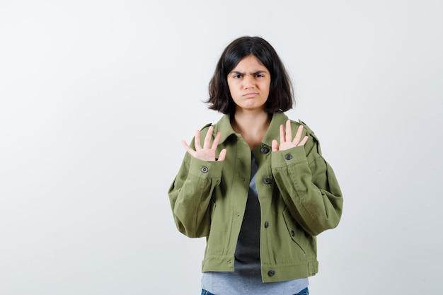 灰色のセーター、カーキ色のジャケット、降伏のジェスチャーで手のひらを上げて真剣に見えるジーンズパンツ、正面図の若い女の子。