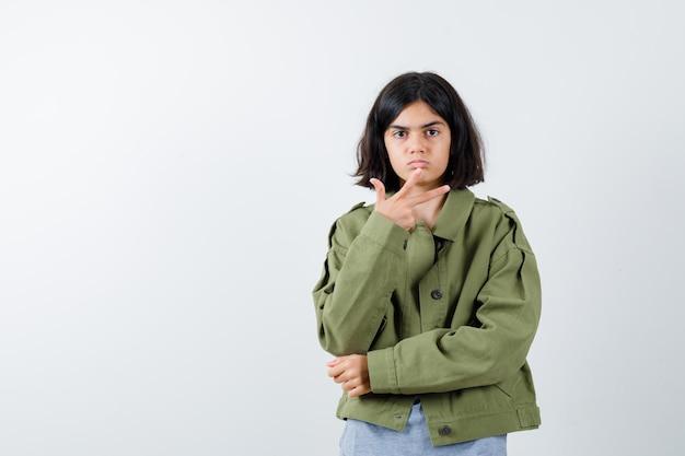灰色のセーター、カーキ色のジャケット、カメラに向かって手を伸ばして真剣に見えるジーンズパンツ、正面図の若い女の子。