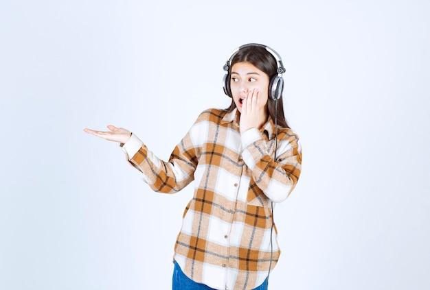 白い壁に何かを示しているヘッドフォンの少女。