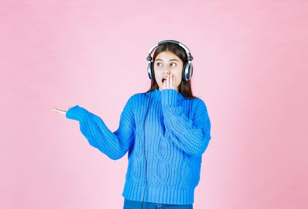 ピンクの上に立っているヘッドフォンの少女。