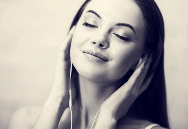 집에서 편안한 휴대 전화와 함께 헤드폰에 어린 소녀. 단색화.