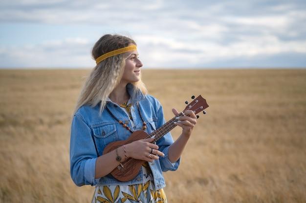 Молодая девушка в одежде хиппи с гитарой укулеле на фоне золотого поля спелой ржи