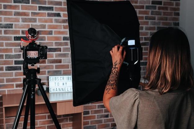 스튜디오에서 카메라 삼각대를 조정하는 20대 소녀