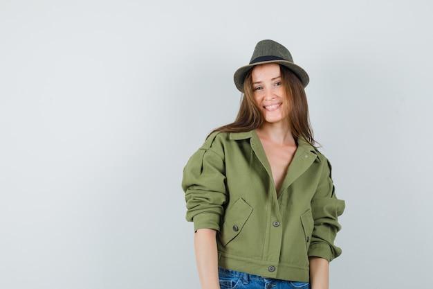 ジャケット、帽子、陽気に見える、正面の若い女の子。