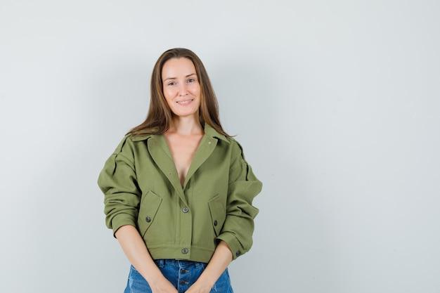 ジャケット、ショートパンツ、魅力的な外観の若い女の子、正面図。