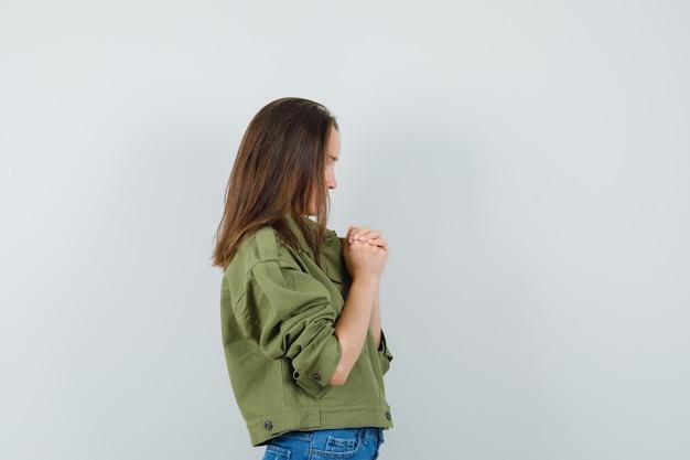 재킷에 어린 소녀, 손을 꽉 쥐고 희망을 찾고 반바지.