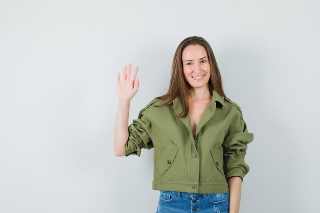 ジャケットを着た少女、挨拶と陽気に見えるために手を振るショートパンツ、正面図。