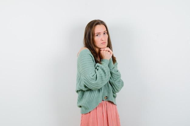 ニットウェアの少女、祈りの位置で手を握りしめているスカート、肩越しに見て真剣に見える、正面図。 無料写真