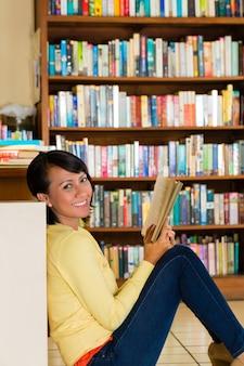 Молодая девушка в библиотеке читает книгу