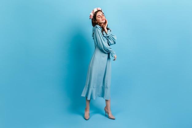 파란색 벽에 포즈를 취하 긴 드레스에 어린 소녀. 머리카락에 장미가 달린 모델이 부드럽게 얼굴에 닿습니다.