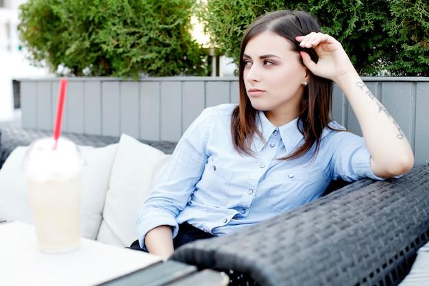 Молодая девушка в офисной одежде ждет партнера в кафе