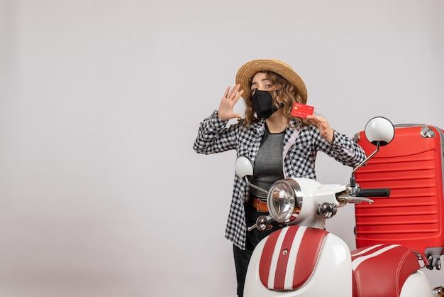 Молодая девушка в панамской шляпе держит карточку и зовет кого-то, стоящего возле красного мопеда