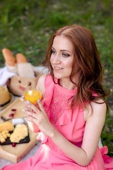 公園で夏のピクニックを持つジュースを保持している公園で若い女の子。リラックスしたコンセプト