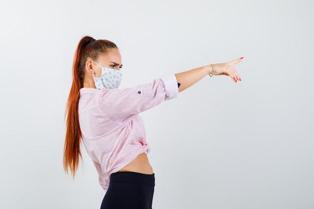 Молодая девушка в розовой блузке, черных штанах, маска, указывающая вправо указательным пальцем и сосредоточенная, вид спереди.