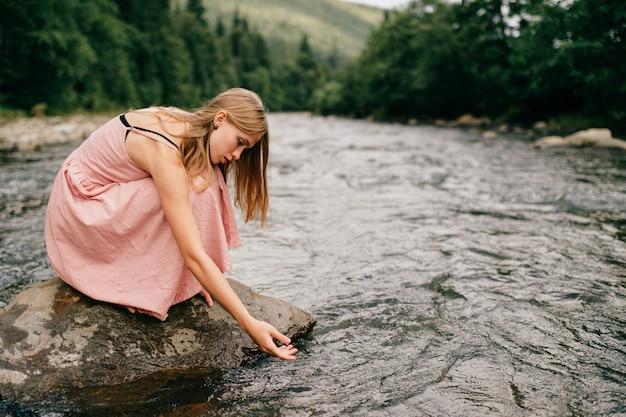 川の石に座っていると水に触れるピンクのドレスの少女