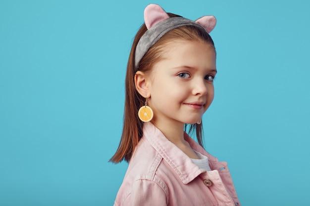 Молодая девушка в розовой куртке позирует очаровательно на синем студийном фоне