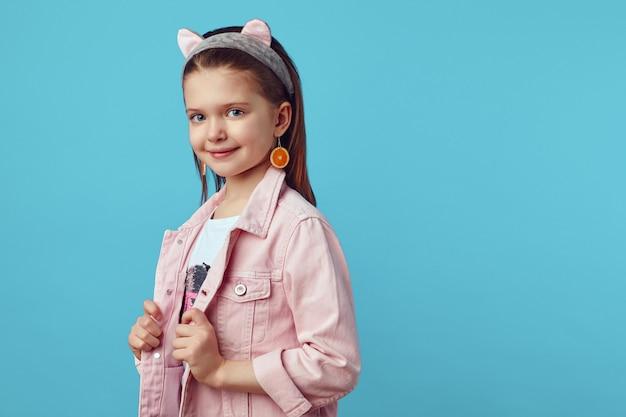 Молодая девушка в розовой куртке очаровательно позирует на синем студийном фоне