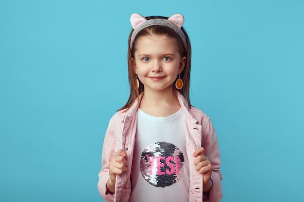 Молодая девушка в розовой куртке показывает свою белую рубашку с надписью да