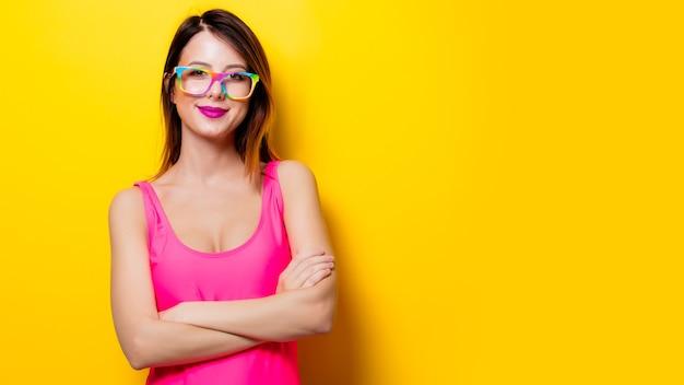 Молодая девушка в розовом цельном купальном костюме с очками