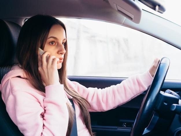 Молодая девушка в розовом pite говорит по телефону, сидя в машине.