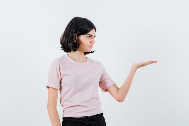 ピンクのtシャツと黒のズボンの少女が想像上の何かを持って真剣に見えるように手を伸ばします