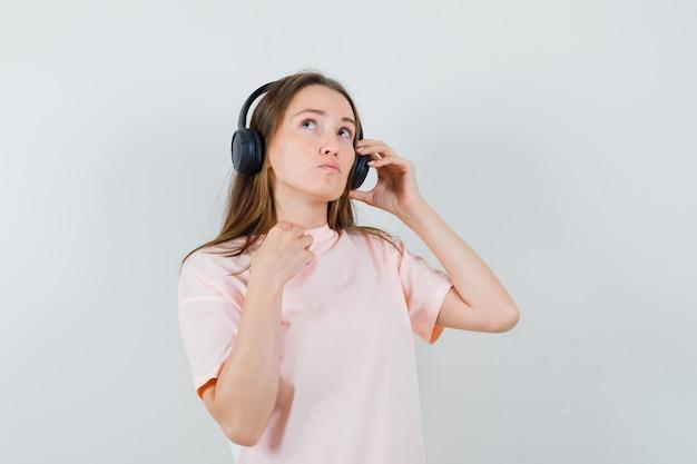 ヘッドフォンで音楽を楽しんで、物思いにふける、正面図を見てピンクのtシャツの少女。