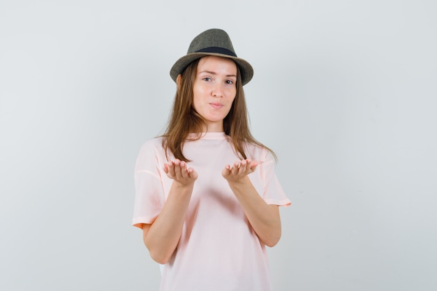 ピンクのtシャツを着た若い女の子、手のひらに何かを持っているふりをして帽子、正面図。