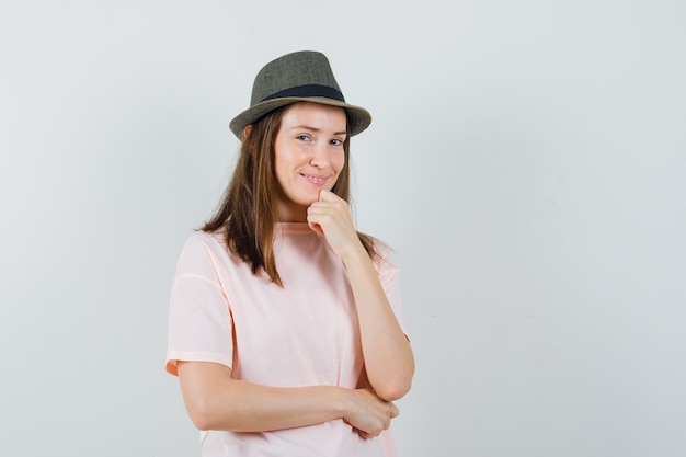 ピンクのtシャツを着た若い女の子、拳で顎を支え、自信を持って見える帽子、正面図。