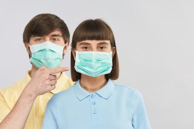 Молодая девушка в защитной маске и красивый парень указывают на нее пальцем, защита от коронавируса, копировальное пространство