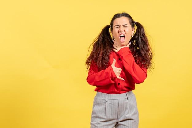 黄色の喉の痛みを持っている赤いブラウスの少女