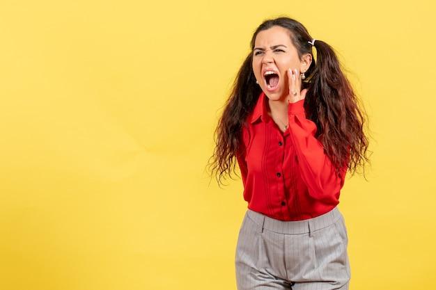 Молодая девушка в красной блузке громко зовет кого-то по желтому