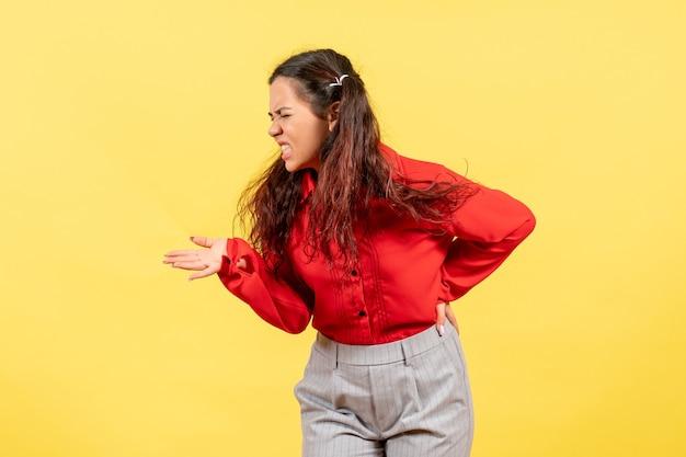 Молодая девушка в красной блузке страдает от боли в спине на желтом