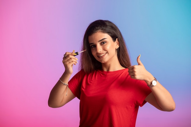 化粧をしている赤いシャツの少女。
