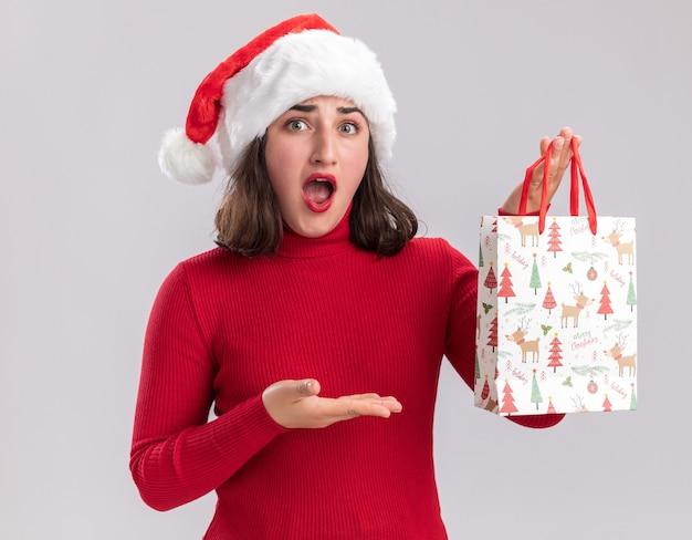 赤いセーターとサンタの帽子をかぶった少女は、白い背景の上に立っている彼女の手の腕を提示して驚いて見えるクリスマスプレゼントとカラフルな紙袋を保持しています