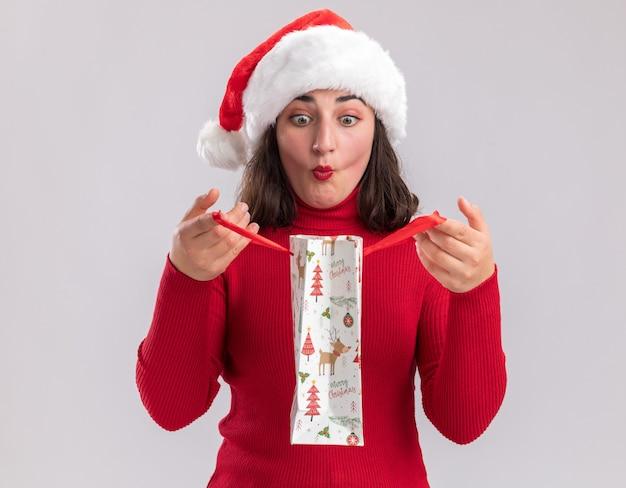 赤いセーターとサンタの帽子をかぶった若い女の子がクリスマスプレゼントとカラフルな紙袋を持って白い背景の上に立って驚いて中を見て