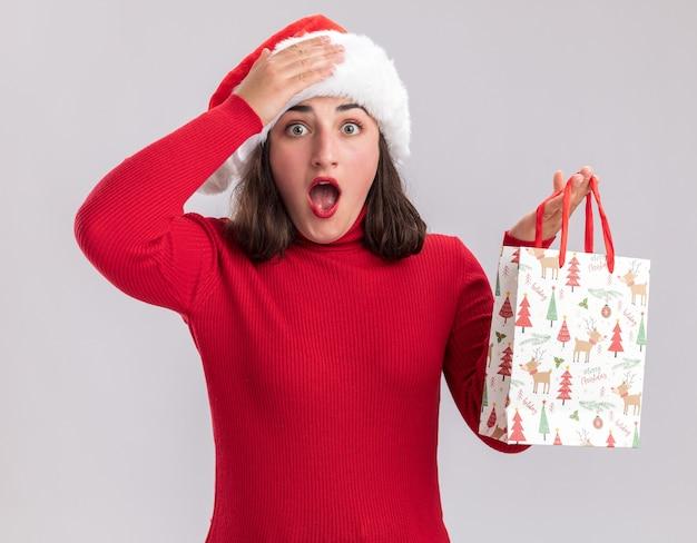 빨간 스웨터와 산타 모자 크리스마스 선물 다채로운 종이 가방을 들고 어린 소녀 놀라게 하 고 흰 벽 위에 서있는 그녀의 손에 손으로 깜짝 놀라게