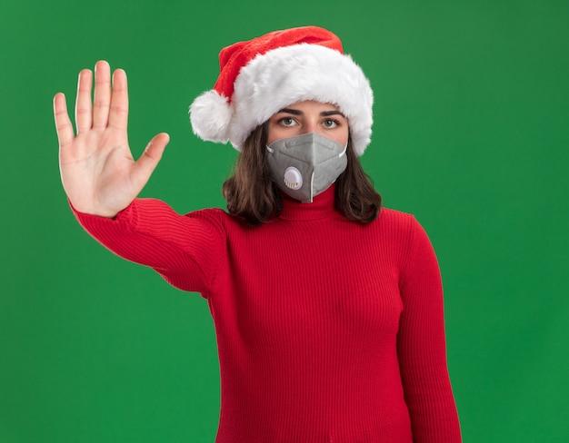 Молодая девушка в красном свитере и шляпе санта-клауса в защитной маске для лица с серьезным лицом делает стоп-жест рукой, стоящей над зеленой стеной