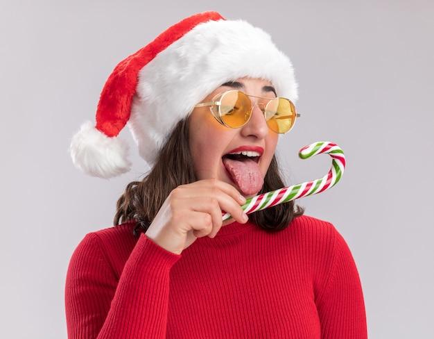 Молодая девушка в красном свитере и шляпе санта-клауса в очках держит конфету, пытаясь попробовать ее счастливой и радостной, стоя на белом фоне