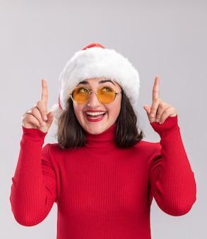 빨간 스웨터와 산타 모자에 어린 소녀 흰색 배경 위에 서 검지 손가락으로 행복하고 즐거운 가리키는 찾고 안경